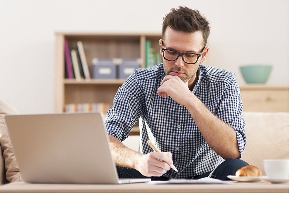 man writing at his computer