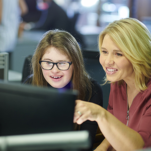 Two women looking a computer together.