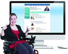 A woman sitting in a wheelchair in front of a computer screen with an Easy Read website. She is giving a thumbs up.